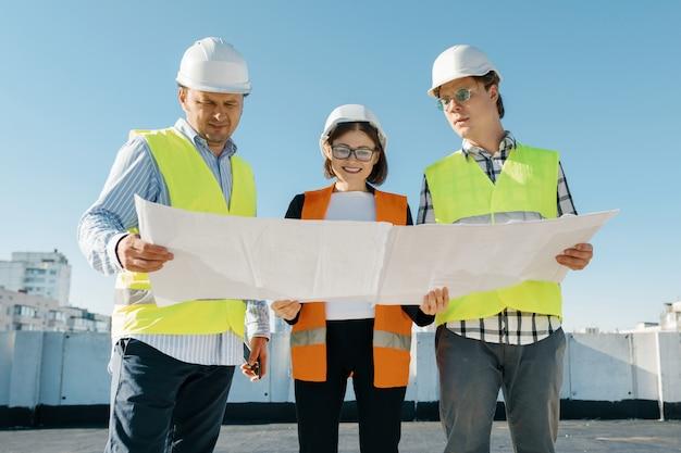 Equipe de engenheiros de construtores em um canteiro de obras, lendo o projeto Foto Premium