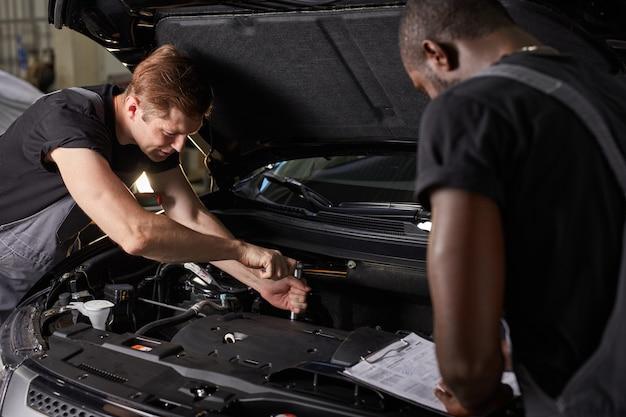 Equipe de homens africanos e caucasianos trabalhando juntos no serviço automotivo Foto Premium