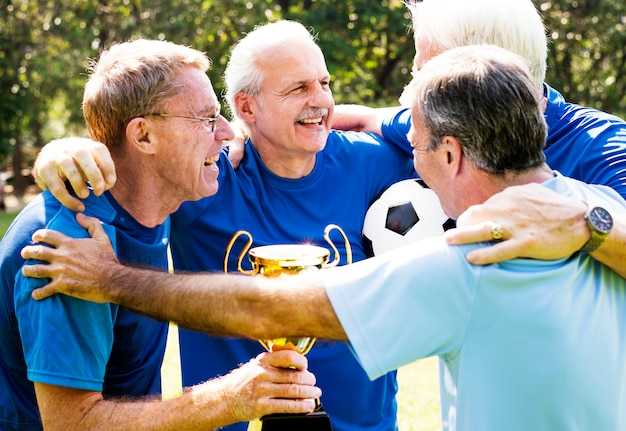 Equipe de jogadores de futebol maduros, vencendo a taça Foto Premium