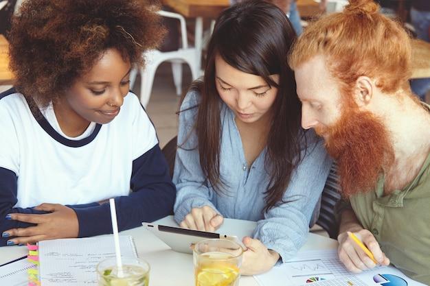 Equipe de jovens de diversas etnias fazendo brainstorming, discutindo planos de negócios e ideias de seu projeto comum, parecendo entusiasmados. Foto gratuita