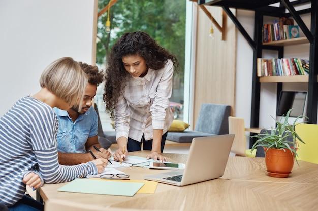 Equipe de jovens empreendedores criativos trabalhando no projeto de equipe, olhando através de informações sobre lucros no laptop, escrevendo idéias no papel. brainstorm conceito. Foto gratuita