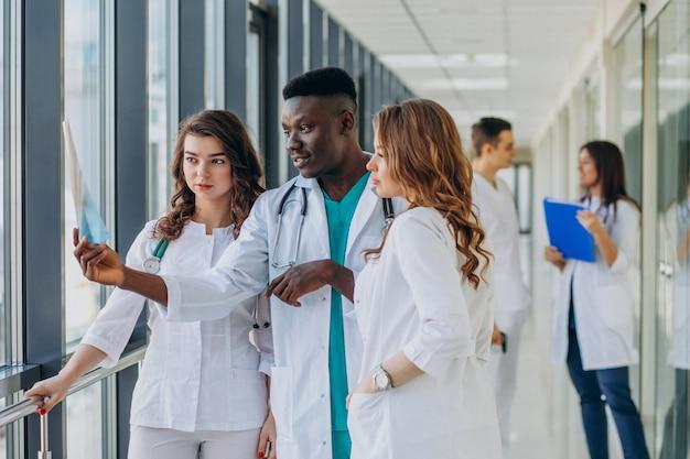 Equipe de jovens médicos especialistas em pé no corredor do hospital Foto gratuita