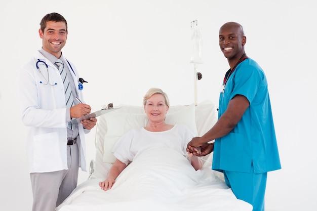 Equipe de médicos com um paciente sorrindo para a câmera Foto Premium