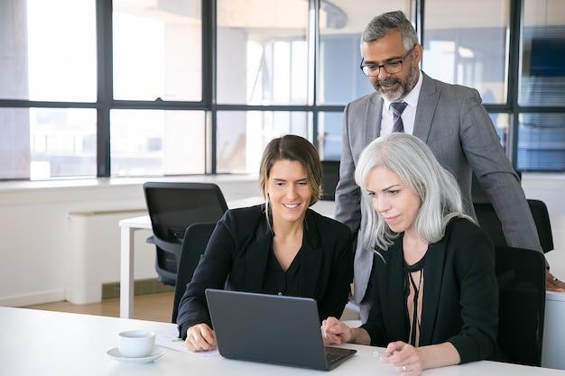 Equipe de negócios alegre assistindo apresentação no laptop, sentado no local de trabalho, olhando para o visor e sorrindo. copie o espaço. conceito de reunião de negócios Foto gratuita