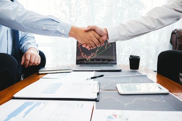 Equipe de negócios, apertando as mãos com negociação de investimento empresarial discutindo e análise gráfico negociação no mercado de ações, conceito de gráfico de ações Foto Premium