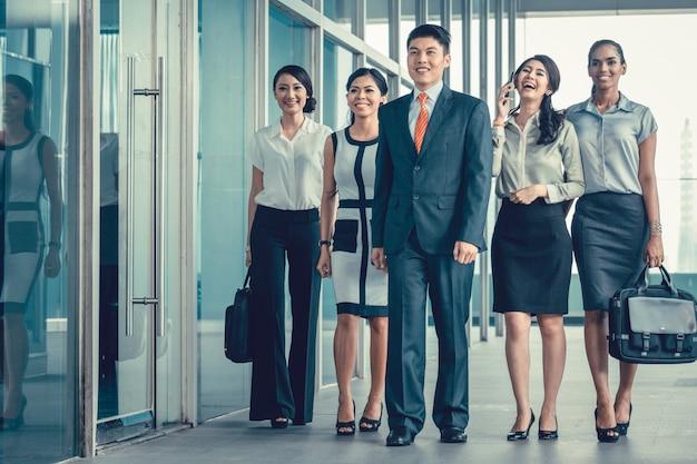 Equipe de negócios asiáticos de executivos andando no escritório Foto Premium