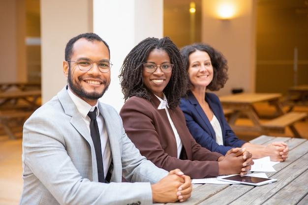 Equipe de negócios diversos felizes posando no café de rua Foto gratuita