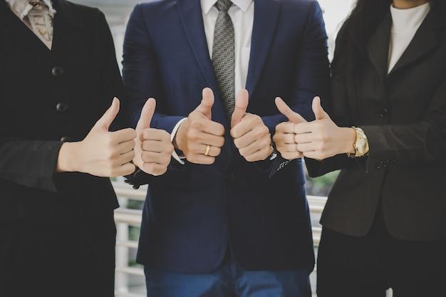 Equipe de negócios em frente ao escritório com negócios bem sucedidos com mostrando polegares acima Foto gratuita
