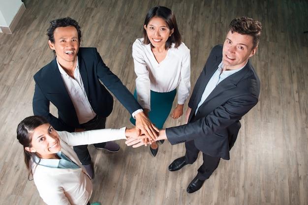 Equipe de negócios feliz com mãos juntas no salão Foto gratuita