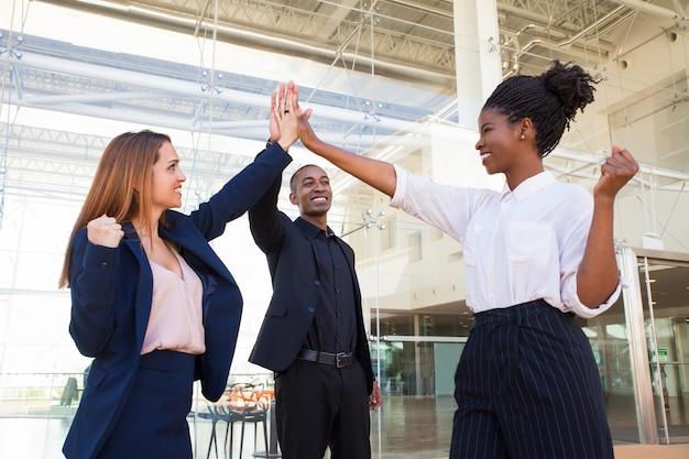 Equipe de negócios forte feliz fazendo mais cinco no escritório Foto gratuita