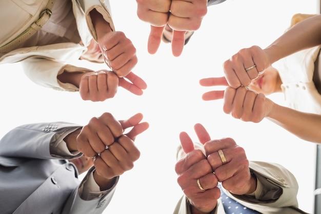 Equipe de negócios olhando para a câmera mostrando polegares para cima Foto Premium