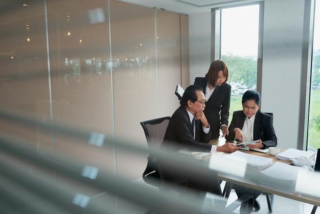 Equipe de negócios vietnamita discutindo documento no computador tablet Foto gratuita