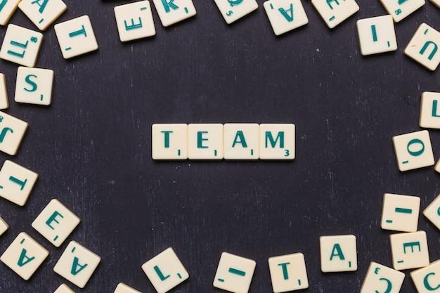 Equipe de palavras em letras scrabble sobre pano de fundo preto Foto gratuita