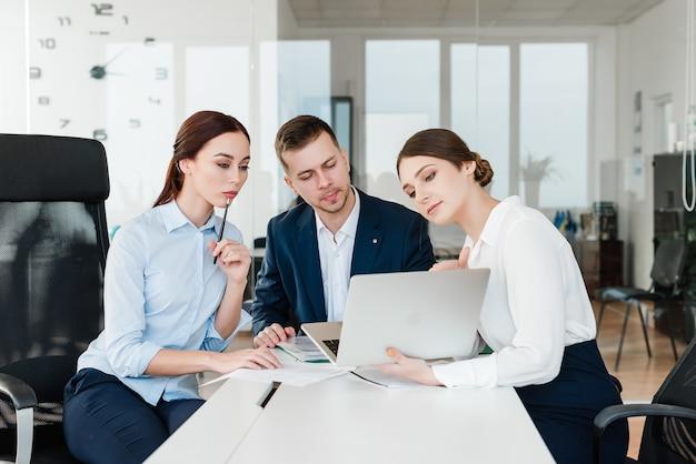 Equipe de profissionais olhando para laptop e discutindo negócios no escritório Foto Premium