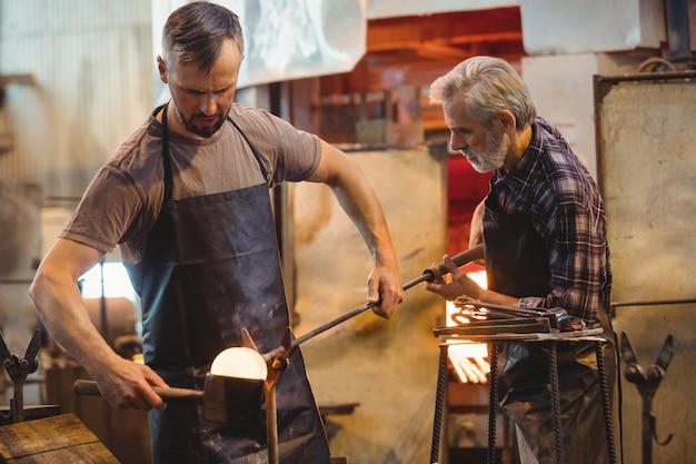 Equipe de soprador de vidro formando e moldando um vidro fundido Foto gratuita