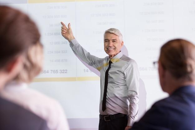 Equipe de sorriso do professor sênior business coaching Foto gratuita