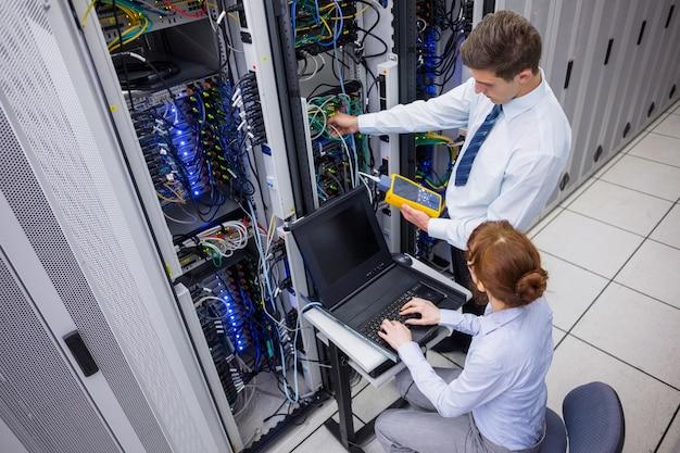 Equipe de técnicos que utilizam o analisador de cabo digital em servidores Foto Premium