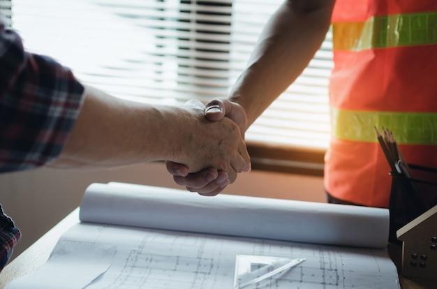 Equipe, de, trabalhador construção, apertando mãos, com, cliente Foto Premium
