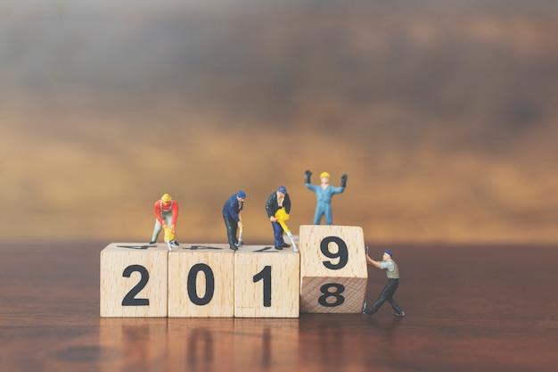 Equipe de trabalhadores em miniatura, construindo o bloco de madeira número 2019 Foto Premium