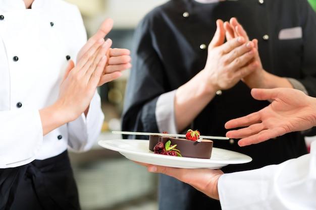 Equipe do chef na cozinha do restaurante com sobremesa Foto Premium