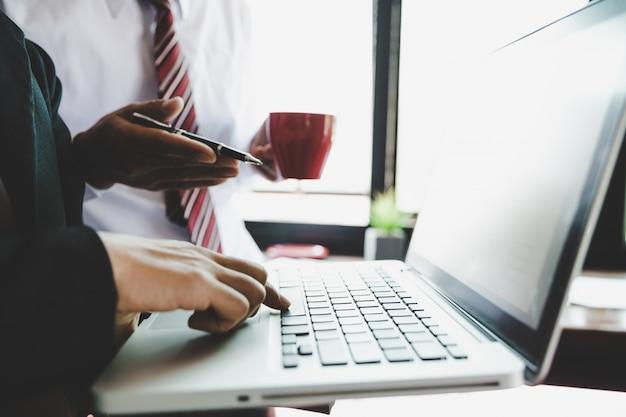 Equipe do negócio que analisa tabelas e gráficos da renda com o computador portátil moderno. Foto gratuita