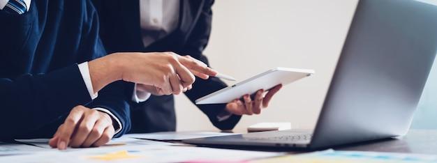 Equipe do negócio que usa a tabuleta e o laptop para trabalhar no escritório. Foto Premium
