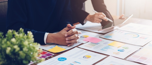 Equipe do negócio que usa a tabuleta que trabalha na tabela e em originais financeiros no escritório. Foto Premium
