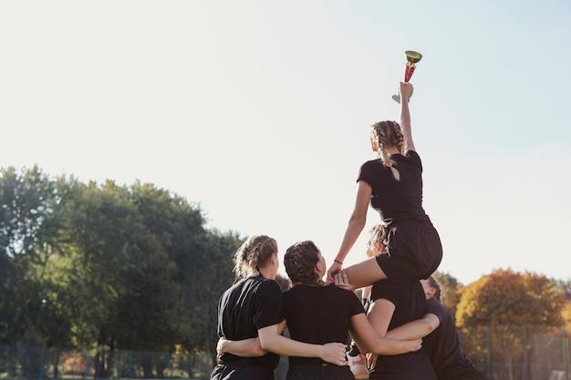 Equipe feminina de vista traseira, ganhando um troféu Foto gratuita