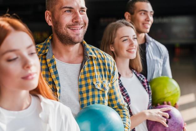Equipe jovem feliz, segurando bolas de boliche Foto gratuita