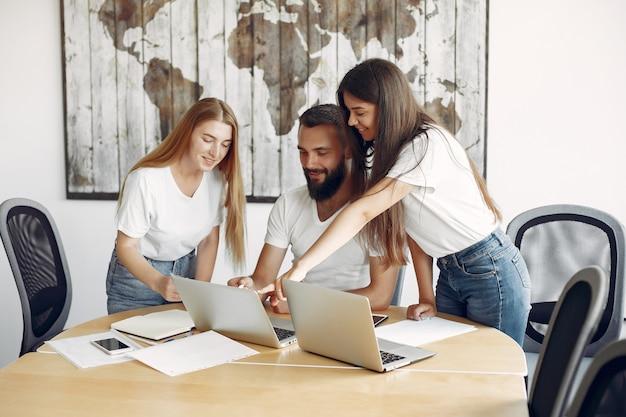 Equipe jovem trabalhando juntos e use o laptop Foto gratuita