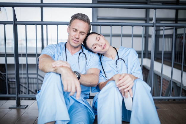 Equipe médica cansada adormecer no chão do hospital Foto Premium