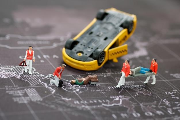 Equipe médica de emergência em miniatura para ajudar pessoas acidente de carro. Foto Premium