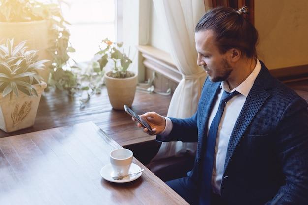 Equipe o assento na barra do café e a escrita de uma mensagem no telefone celular durante a ruptura de café. Foto Premium