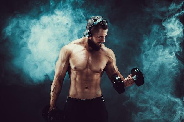 Equipe os músculos do treinamento com halteres no estúdio em fundo escuro com fumaça. Foto Premium