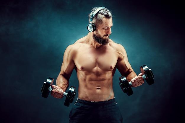Equipe os músculos do treinamento com halteres no estúdio em fundo escuro. Foto Premium