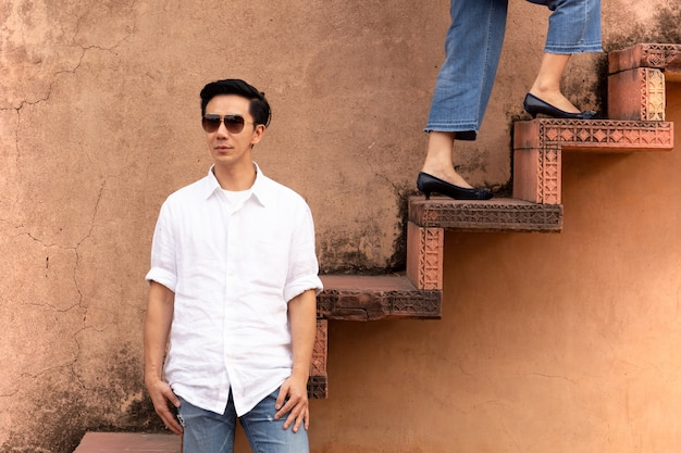 Equipe os óculos de sol vestindo que estão na escadaria com a mulher que anda acima das escadas. Foto Premium