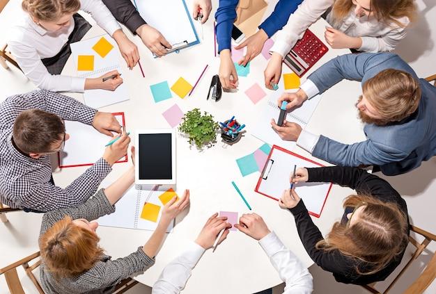 Equipe sentada atrás da mesa, verificando relatórios, conversando. vista do topo. Foto gratuita