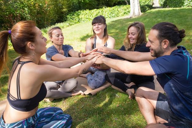 Equipe unida de amigos se unindo para treino ao ar livre Foto gratuita