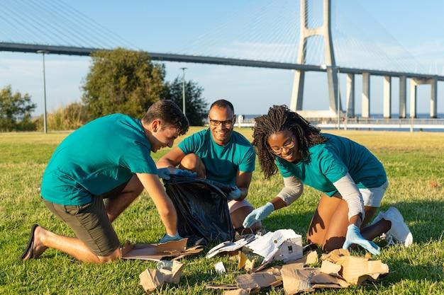 Equipe voluntária feliz que limpa a área verde da cidade Foto gratuita