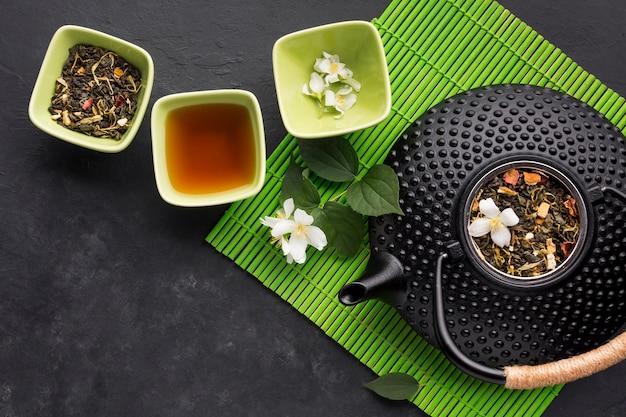 Erva de chá seco com flor de jasmim branco no plano de fundo texturizado Foto gratuita