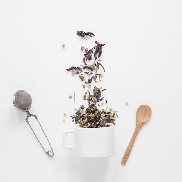 Ervas de chá caindo do copo com filtro e colher no pano de fundo branco Foto gratuita