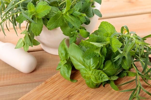 Ervas frescas com um almofariz e pilão Foto gratuita