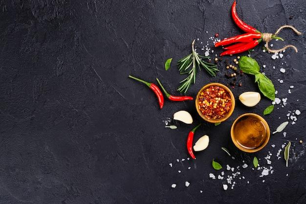 Ervas frescas e especiarias na mesa de pedra preta Foto Premium