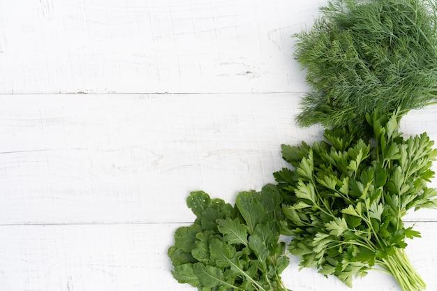 Ervas frescas em uma mesa de madeira branca Foto Premium