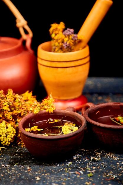Ervas medicinais na mesa de madeira preta, fitoterapia Foto Premium