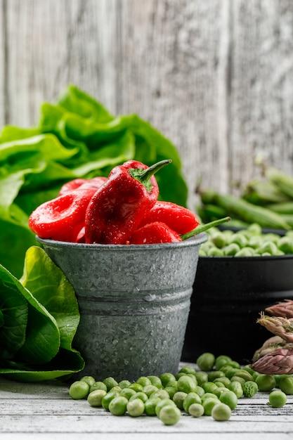 Ervilhas e pimentos com alface, vagens verdes, aspargos, bok choy em baldes na parede de madeira suja, vista lateral. Foto gratuita