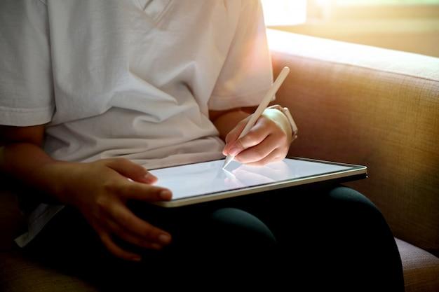 Esboços do desenho da mão da menina com a tabuleta moderna de superfície do écran sensível ao sentar o sofá. Foto Premium
