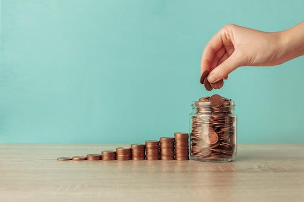 Escada de moedas, uma jarra e uma mão Foto Premium