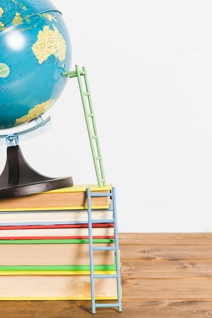 Escada de papel no mapa global terrestre stand bola e livros na mesa de madeira Foto gratuita