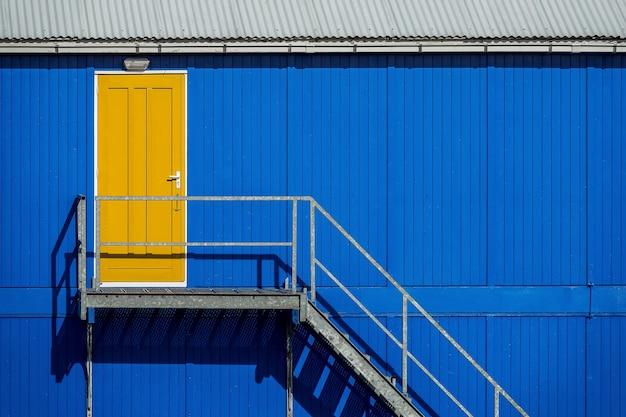 Escada perto da parede azul de uma garagem que leva à porta amarela Foto gratuita